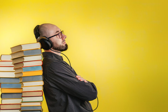 Education and modern technologies. The concept of audio books. A man in glasses, shirt, and earphones leaned against stacks of books. Yellow background. Copy pace
