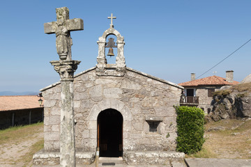 medieval church with cruziro in front in Galicia