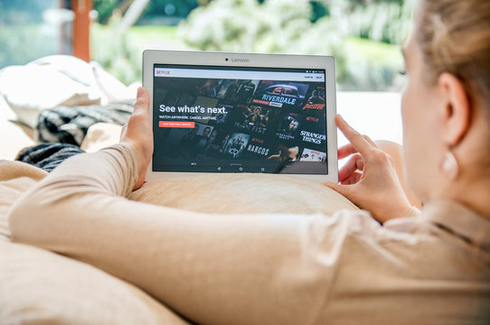 WROCLAW, POLAND- APRIL 10th, 2017:  Woman launches Netflix application on Lenovo tablet. Netflix is an American entertainment company specializes in streaming media and video-on-demand online