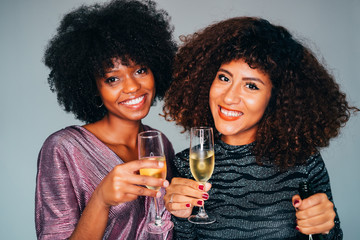 Two Young Beautiful African American women holding a glass of champagne and toasting. Cheers! Wall mural