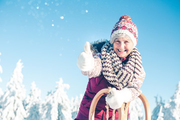 Mature woman with gray hair and winter cap is standing in beautiful winter landscape with sledge