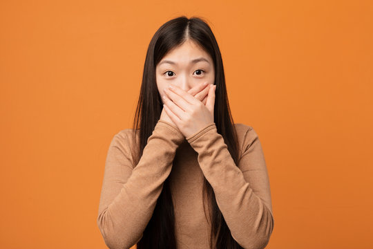 Young pretty chinese woman shocked covering mouth with hands.