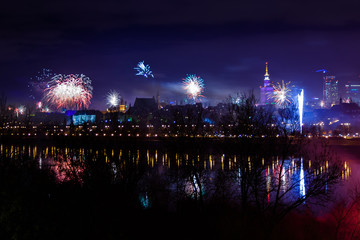 New Year's fireworks show in Warsaw, Poland at night, view from the Vistula River and city center