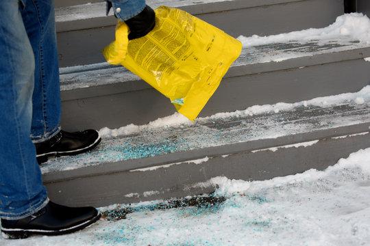 winter safety -  a worker putting salt on a snowy  stairway