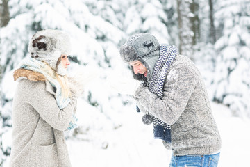 young, pretty, in love couple with winter cap and scarf in winter landscape makes a snowball fight and blows snow