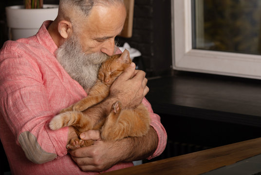 Senior man holding cute red cat at home. Man and cat hugging.