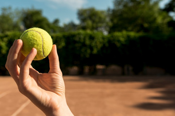hand holds green tennis ball