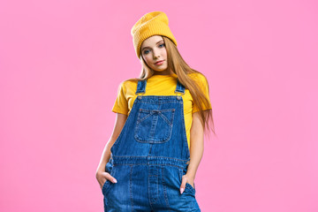 Portret a pretty girl in denim overalls and a yellow hat on a pink background. Fashionista lady student smiling . Bright trendy studio fashion image of sexy model, wearing neon bright color block