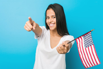 Young hispanic woman holding a united states flag cheerful smiles pointing to front.
