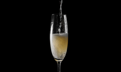 pour champagne into an empty glass. on a black background
