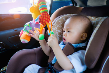 Cute little Asian 1 year old toddler baby boy child trying to reach colorful toy, Kid sitting & playing toy in car seat, toddler is having fun, Happy little traveller safety, road trip concept