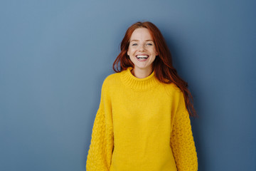 Joyful young redhead woman laughing at camera Fotobehang