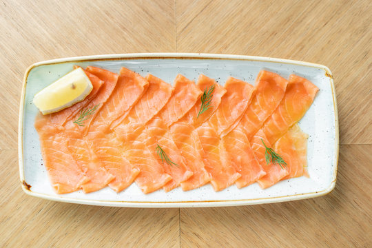 Restaurant menu. Plate with slightly salted and smoked salmon or trout fillet on wooden table background. Thin slices of red fish with lemon close up