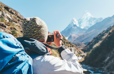 Young hiker backpacker female taking photo mountain view during high altitude Acclimatization walk. Everest Base Camp trekking route, Nepal. Active vacations concept image