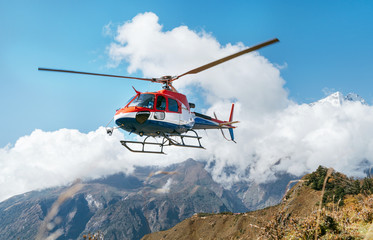 Zelfklevend Fotobehang Helicopter Medical Rescue helicopter landing in high altitude Himalayas mountains. Safety and travel insurance concept image.