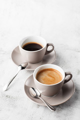 Canvas Prints Cafe Two white cups of hot black coffee with milk isolated on bright marble background. Overhead view, copy space. Advertising for cafe menu. Coffee shop menu. Vertical photo.