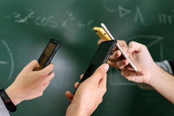 Students using mobile phones in classroom with a chalkboard in the background .