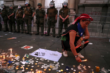 A person lights a candle as members of the security forces take position during a demonstration in Santiago