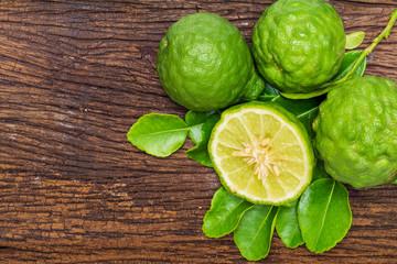 Fresh bergamot fruit with bergamot leaves on old wooden background.