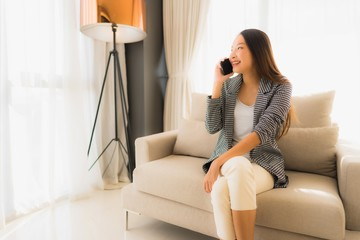 Portrait beautiful young asian women using talking mobile phone and sitting on sofa chair
