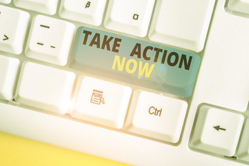 Text sign showing Take Action Now. Business photo text asking someone to start doing Good perforanalysisce Encourage White pc keyboard with empty note paper above white background key copy space