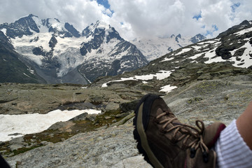 hiking boot with a background of snow capped mountains