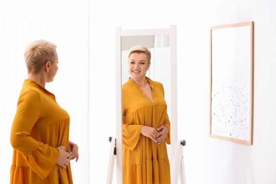 Beautiful mature woman looking at herself in large mirror indoors