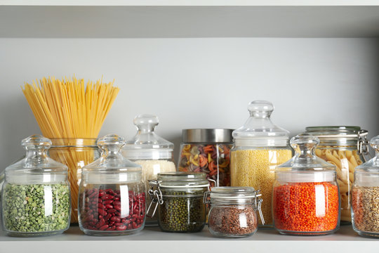 Glass jars with different types of groats and pasta on white shelf