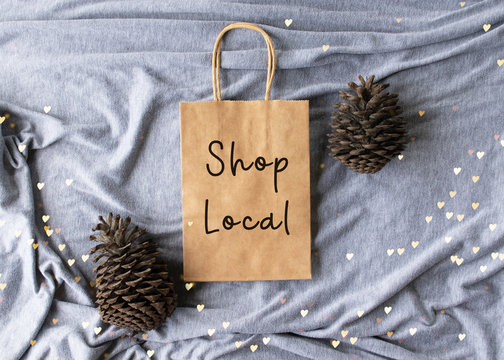 """""""Shop Local"""" text on a plain brown paper bag flat lay with pine cones and hearts- Christmas shopping message concept"""