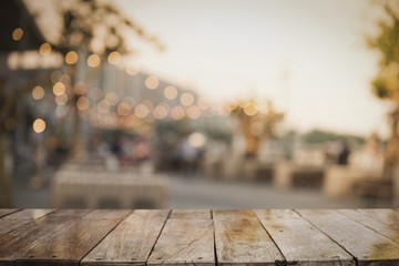 3D Rendering, Wooden top table with bokeh light effect and blur outdoor restaurant on background