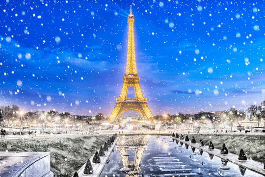 PARIS, FRANCE - DECEMBER 09,2016: Eiffel Tower shows a light show in Paris on a snowy winter night. Eiffel Tower is most visited monument in France and use 20,000 light bulbs in the night show