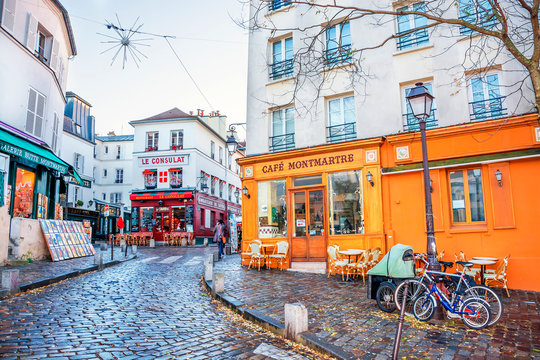 PARIS, FRANCE - DECEMBER 11,2016: Typical French street in Montmartre district with small houses are located cafes, restaurants and art galleries.
