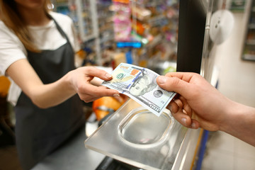 Young man paying for goods in supermarket, closeup
