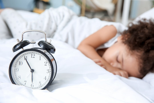 Little African-American girl with alarm clock sleeping in bed