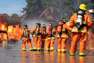 Firemen wearing fire fighter suit for safety and using water, extinguisher to fighting with fire flame in an emergency situation.
