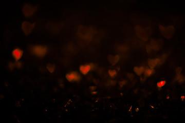 Dark vintage abstract background with orange bokeh defocused lights. Heart shape