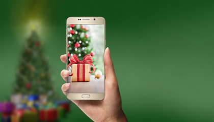 phone with a Christmas picture on the screen on a green background with a Christmas tree