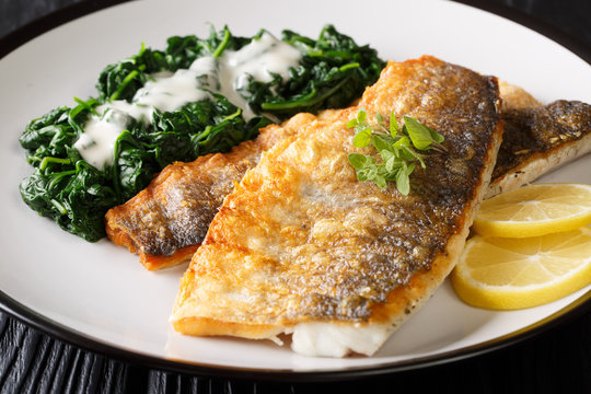 Tasty grilled sea bass fillet with spinach and lemon close-up on a plate. horizontal