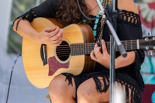 a close up view on musician woman playing the guitar, hands of female guitarist on outdoor stage during a live music gig in nature