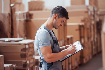 Storage worker in uniform and notepad in hands checks production