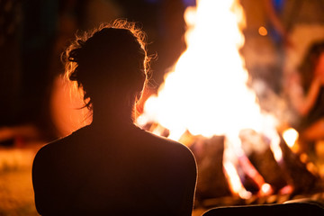 silhouette of a man with long hair sitting in the front of the fire, seen from behind during dark night campfire, blurred background