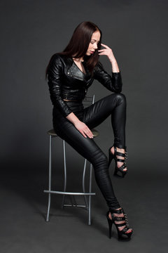 portrait of a young dark-haired girl on a dark background sitting on a bar stool with dark leather pants, jacket and bra