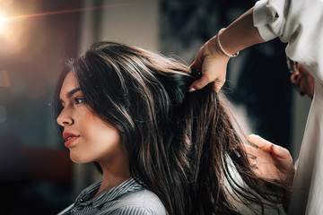 Tuinposter Kapsalon Hairstylist Fixing Woman's Hair