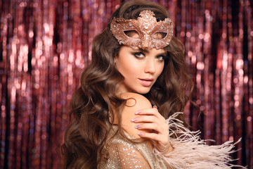 Fotorolgordijn Carnaval Christmas holiday party. Beautiful brunette with Healthy wavy hair. Fashion Beauty Girl with carnival mask Isolated on golden bokeh lights Background. Glamour Makeup. Jewelry copy space. Hairstyle.