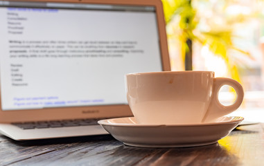 A cup of coffee against a laptop screen. Writing a journal concept