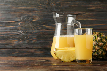 Pineapple, glass jug and glass with juice on wooden background, space for text