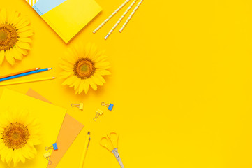 Fotomurales - Top view flat lay of workspace desk styled design with sunflowers notebook diary pencils pen scissors on yellow background. Autumn or summer Concept. Sunflower natural background. Stationery
