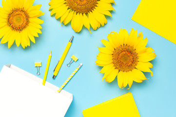 Fototapete - Top view flat lay of workspace desk styled design with sunflowers, white paper bag pencils pen notebook diary paper clips on blue background. Education concept Stationery. Sunflower natural background