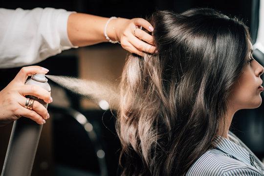 Hairstylist Spraying Woman's Hair