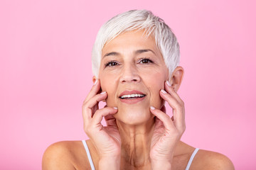 Portrait of beautiful senior woman touching her perfect skin and looking at camera. Closeup face of mature woman with wrinkles massaging face isolated over pink background. Aging process concept.